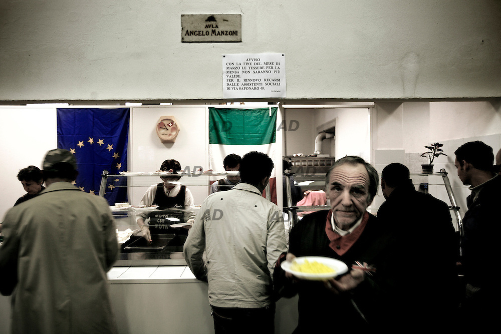 """The canteen in via Saponaro.*** General Caption *** The dormitory in via Saponaro, Milan, managed by the foundation """"Fratelli di San Francesco"""". The Foundation handles many social services, while respecting the dignity of the person and the duty of social solidarity, providing support to people in difficulty, and individual freedom of choice between the benefits to be paid. The association provide  beds in dormitories, canteens and medical ambulatories for those who need.The dorms, places long associated with the reception of desperate immigrants and confused, now representing an impressive number of fellow citizens that the frenzy has collapsed on him. Now the """"stereotype"""" is that man in his fifties, separate food to pass to his wife and children, but suddenly precarious after the company where he worked for a living was bought by a multinational with the logic of """"cutting the staff and production shifted to the east. Possibility of finding a job that can guarantee the previous status, nothing. Ability to work out, certainly less than the myriad of twenty fresh university hyper specialized language and computer skills with years of flying experience."""