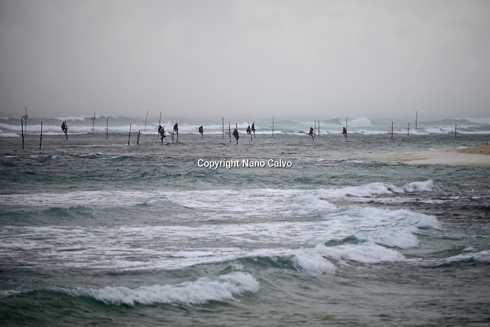 Stilt fishermen in Ahangama coast with rough sea, Sri Lanka