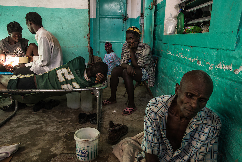 RENDEL, HAITI - OCTOBER 12, 2016:  The small clinic in Rendel, Haiti is overflowing with Cholera patients, and more keep coming. For days, aid groups and officials have warned of a coming Cholera outbreak that could affect as many as 500,000 Haitians.  The town of Rendel and its surroundings, which once sheltered 25,000 people, is an epicenter of the coming disaster. Heroic nurses care for patients splayed on the floor like silent rag dolls, some resting atop the improvised stretchers they arrived on. Patients vomit and defecate on the floor or into small yellow buckets, too sick to leave their stifling confines. The smell of bile and excrement stings the nostrils. PHOTO: Meridith Kohut for The New York Times