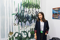 © Licensed to London News Pictures. 06/10/2016. London, UK. Beijing artist, Sophie Zhang shows her work at the preview of Moniker Art Fair, part of London Art Week, taking place at the Old Truman Brewery, near Brick Lane.  Now in its seventh year, the fair embraces contemporary art from emerging and established artists, the majority of whom attend the fair in person in order to meet potential collectors and to show their work. Photo credit : Stephen Chung/LNP