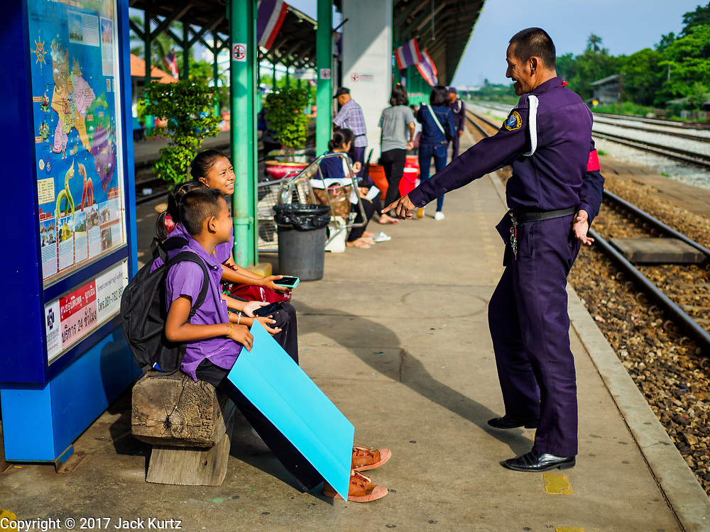 31 MAY 2017 - CHACHOENGSAO, THAILAND: A station security guard chats with middle school students the train station in Chachoengsao, a provincial town about 50 miles and about an hour by train from Bangkok. The train from Chachoengsao to Bangkok takes a little over an hour but traffic on the roads is so bad that the same drive can take two to three hours. Thousands of Thais live outside of Bangkok and commute into the city for work on trains, busses and boats.       PHOTO BY JACK KURTZ