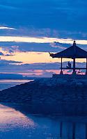 man praying in pagoda at dawn on the Indian Ocean in Bali, Indonesia