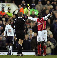Photo: Paul Thomas.<br /> Tottenham Hotspur v Arsenal. Calring Cup, Semi Final 1st Leg. 24/01/2007.<br /> <br /> Kolo Toure (R) of Arsenal is given a yellow card by Graham Poll