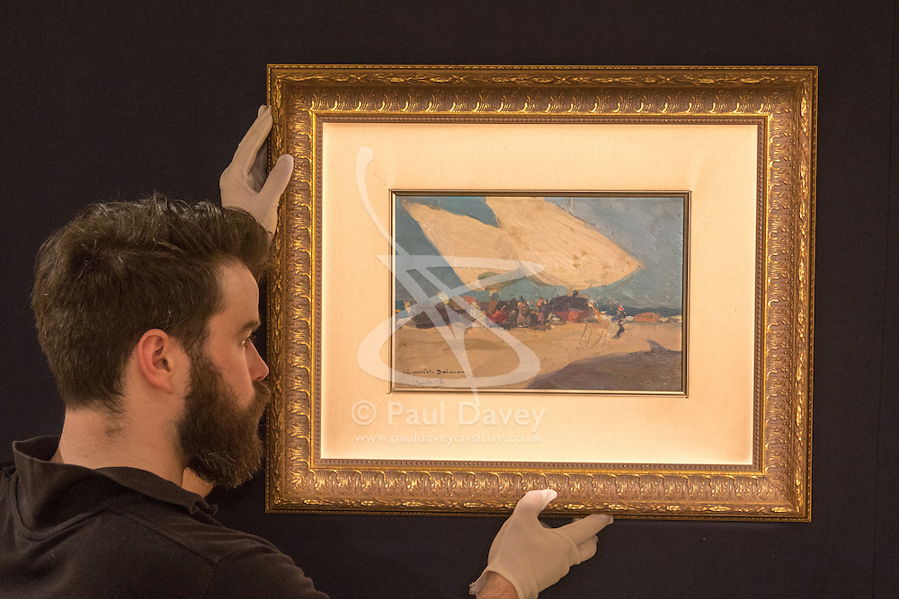 Bonhams, London, February 22nd 2017. Bonhams in London hold a press preview ahead of their 19th century paintings sale, featuring numerous valuable works including:<br /> • 'Children by the shore' by Dorothea Sharp, valued at £60,000-80,000<br /> • Barcas y pescaadores, Playa de Valencia painted by Joaquin Sorolla<br /> • When the Boats Come In by Walter Osborne valued at £100,000-150,000<br /> • A Solicitation by Lawrence Alma-Tadema which is expected to fetch between £30,000-50,000<br /> PICTURED: A gallery porter hangs Barcas y pescaadores, Playa de Valencia painted by Joaquin Sorolla