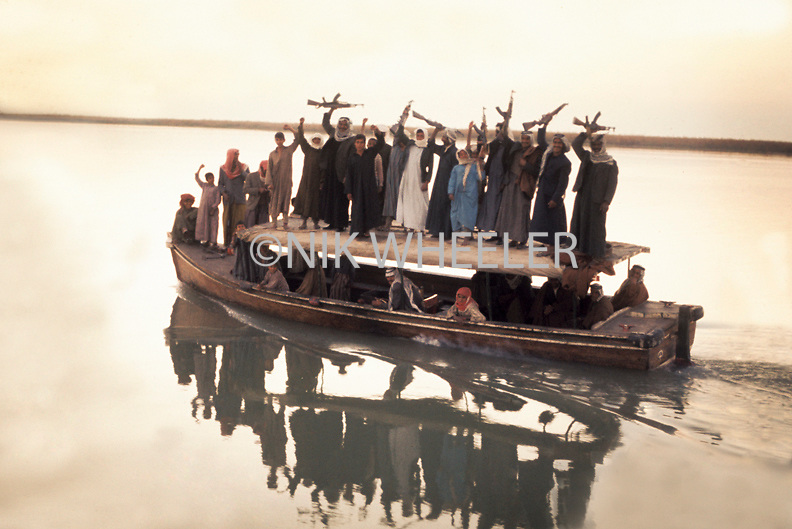 Iraqi Marsh Arabs wave AK 47s from roof of ferry boat to celebrate wedding in the marshes of Southern Iraq