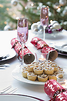 Christmas crackers and mince pies on dining table