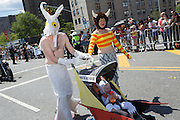 "A family giving homage to the late children's book illustrator Maurice Sendak, in sea creature costumes, and with a sign on their baby buggy ""Where the wild fish are."""