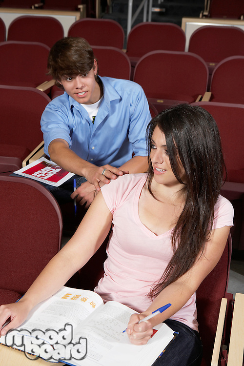 Male college student with hand on girl's shoulder in classroom