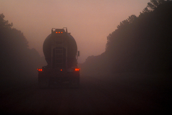 Large liquid transport truck driving through early morning fog