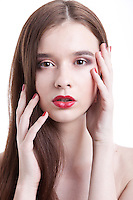 Portrait of beautiful young woman with red lips posing against white background
