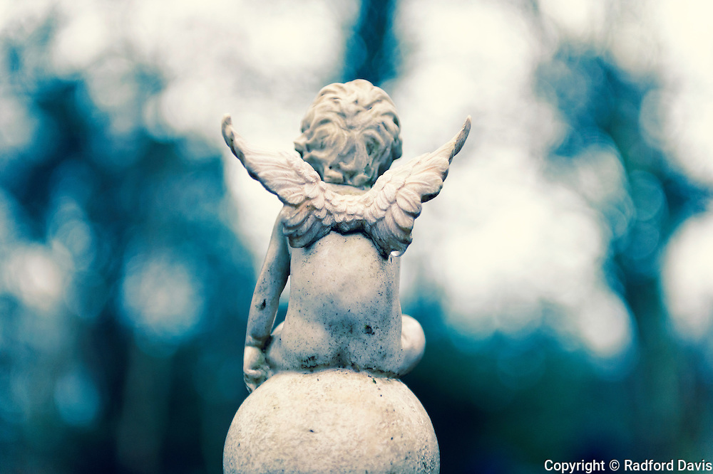 Boy angel on a post at the entrance to an orphanage cemetery in Letterfrack, Ireland
