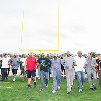 Life Remodeled CEO Chris Lambert football coach Calvin Norman, sponsors and supporters lock arms and walk length of new field during ceremony.