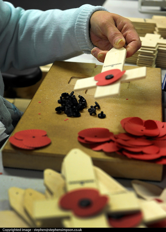 © Licensed to London News Pictures. 07/11/2011. Richmond, UK. A cross is assembled. Red Poppies being made in The Poppy Factory in preparation for sale in 2012, Richmond, Surrey today 7th November.  The factory has been supplying the poppy, crosses and wreathes to the British Legion for almost 90 years. It is staffed by veterans, many whom of which are injured, sick or wounded of all ages. Photo credit : Stephen Simpson/LNP