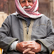 A Syrian man wearing a kuffiyeh and traditional clothes, on a street in Aleppo