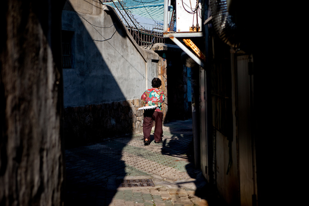 Daegu/South Korea, Republic Korea, KOR, 16.10.2009: Woman walking in an old part of Daegu close to the herbs market for traditional medicine.