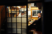 Customers enjoy a drink and some food at a bar in Nonbeiyokocho, an area comprising 47 bars and eateries in trendy Shibuya, Tokyo. Nonbeiyokocho began life immediately after World War II as group of tea houses. Though the alley is just a short walk from the central Shibuya shopping district, the rents are low due to the area being built over a river. Today 47 eateries, each with barely enough room to swing a cat, serve beer, fine wines and good, inexpensive fare.