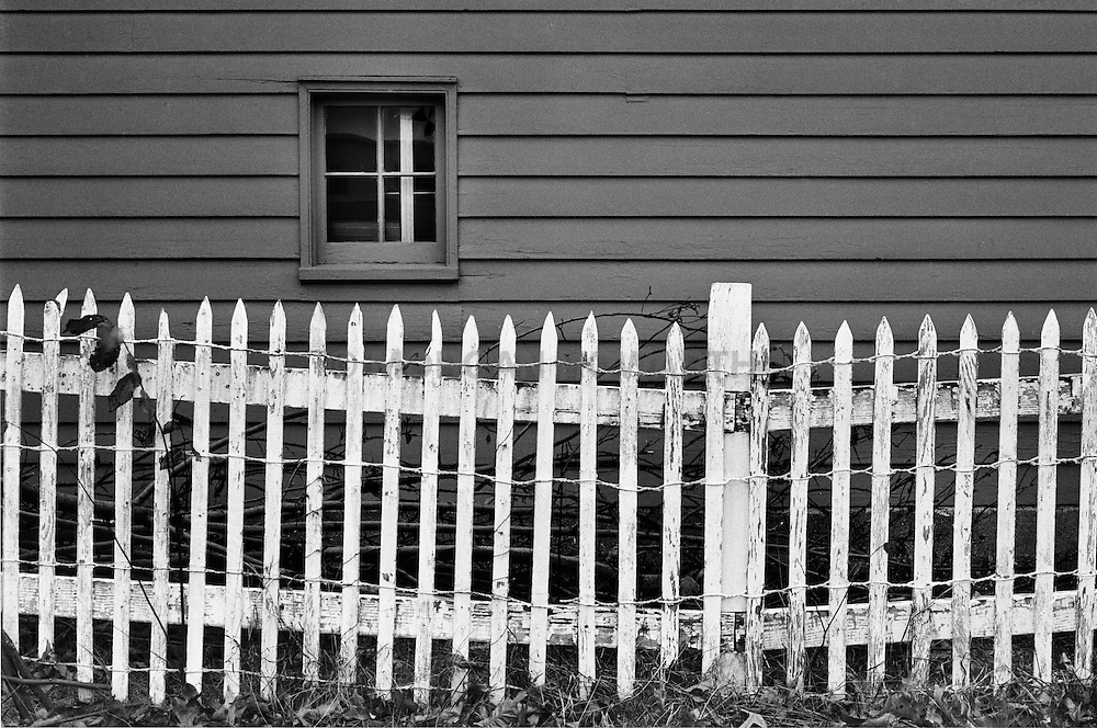 White picket fence with dark grey clapboard house and window