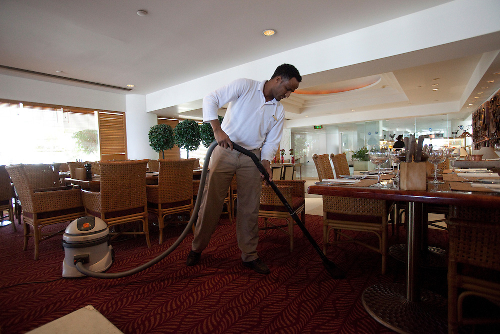 "A sudanese refugee is cleaning the restaurant  of the Royal Beach Hotel on February 28 2011. The municipality hung 1,500 red flags around the city as a sign of warning and put up hundreds of banners reading: ""Protecting our home, the residents of Eilat are drawing the line on infiltration."" Eilat Mayor Meir Yitzhak Halevi said that 10 percent of the city's population was currently made up of migrants and that the residents feel that the city has been conquered...Photo by Olivier Fitoussi."