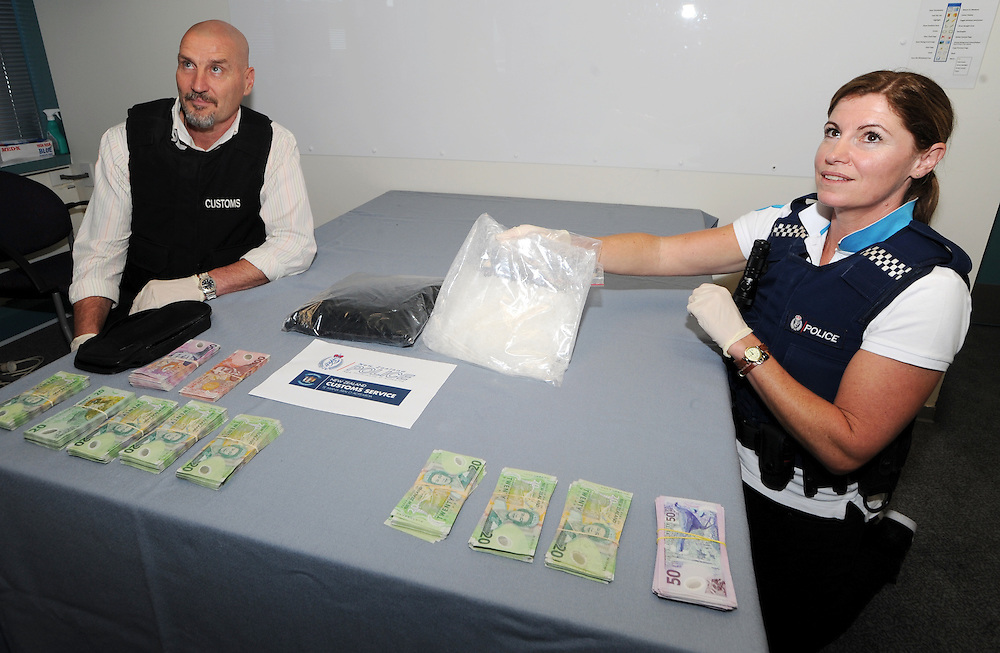 Chief Customs Officer Kirk McPherson, left and Detective Andrea Quinn 2 kilos of methamphetamine valued at $2,000,000 along with $20,000 in cash and two cars taken in a police and customs raids across Wellington, Hutt Valley and Horowhenua netting five arrests, Wellington, New Zealand, Thursday, October 17, 2013. Credit:SNPA / Ross Setford