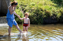 © Licensed to London News Pictures. 25/06/2020. London, UK. A mother and son cool off in the Beverley Brook in Richmond Park in South West London as forecasters predict the hottest day of the year with temperatures expected to reach 33c. Prime Minister, Boris Johnson announces this week that tourism and hospitality including pubs, restaurants and campsites can now reopen from the 4th of July as well as reducing the 2 metre rule to 1 metre. Photo credit: Alex Lentati/LNP <br /> <br /> *Permission Granted by mother*