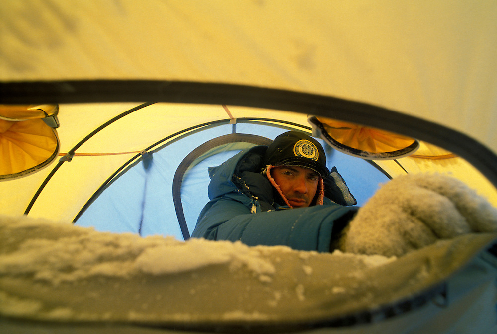 USA, Alaska, Denali National Park, (MR) Rick Ford opens snow-covered tent at 11,000' camp on Mount McKinley (20,320')