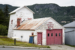 This is how the fire hall located on the grounds of historic Fort William H. Seward in Haines, Alaska looked before the the two-year restoration was begun on the buildling built around 1904. The original 60-foot tower was shortened to approximately half its height in the 1930s for unknown reasons. The restoration included rebuilding a missing 35-foot section of the 60-foot tower whose purpose was to dry fire hoses. The tower restoration was completed by building its four sections on the ground and then hoisting those sections with a crane into place on top of each other.<br /> <br /> Through the years, the historic Fort Seward area, a former U.S. Army post, has been referred to as Fort William H. Seward, Chilkoot Barracks, and Port Chilkoot. The National Historic Landmarks listing record for the fort says that &quot;Fort Seward was the last of 11 military posts established in Alaska during the territory's gold rushes between 1897 and 1904. Founded for the purpose of preserving law and order among the gold seekers, the fort also provided a U.S. military presence in Alaska during boundary disputes with Canada. The only active military post in Alaska between 1925 and 1940, the fort was closed at the end of World War II.&rdquo; <br /> <br /> The bottom portion of the restored fire hall is being leased as commercial space. Due to fire code restrictions there is no public access to the upper portion of the tower. <br /> <br /> The fire hall was restored by owners Joanne Waterman and Phyllis Sage who also own the fort&rsquo;s original guardhouse located next door to the fire hall. That building, now known as the Alaska Guardhouse, is a bed and breakfast.