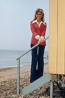 British-born actress Olivia Newton-John poses on the steps of a beach hut in a red jacket and wing-collar blouse, circa 1975.