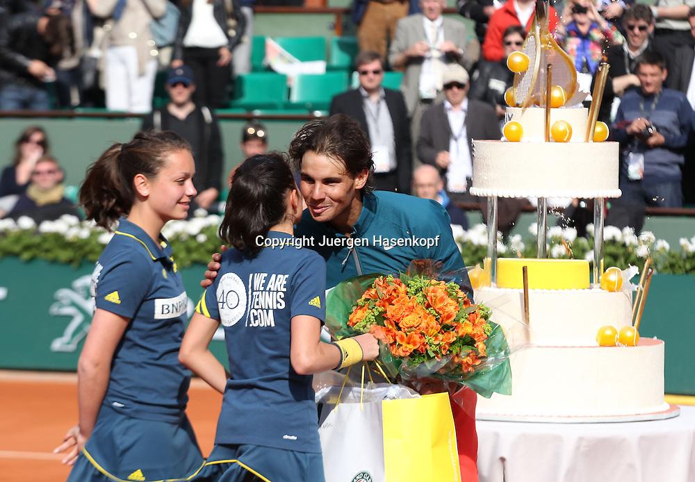 French Open 2013, Roland Garros,Paris,ITF Grand Slam Tennis Tournament, zwei Ballmaedchen ueberreichen Geburtstagskind Rafael Nadal (ESP) eine Blumenstrauss,im Hintergrund steht die riesige Geburtstagstorte<br /> Halbkoerper,Querformat,