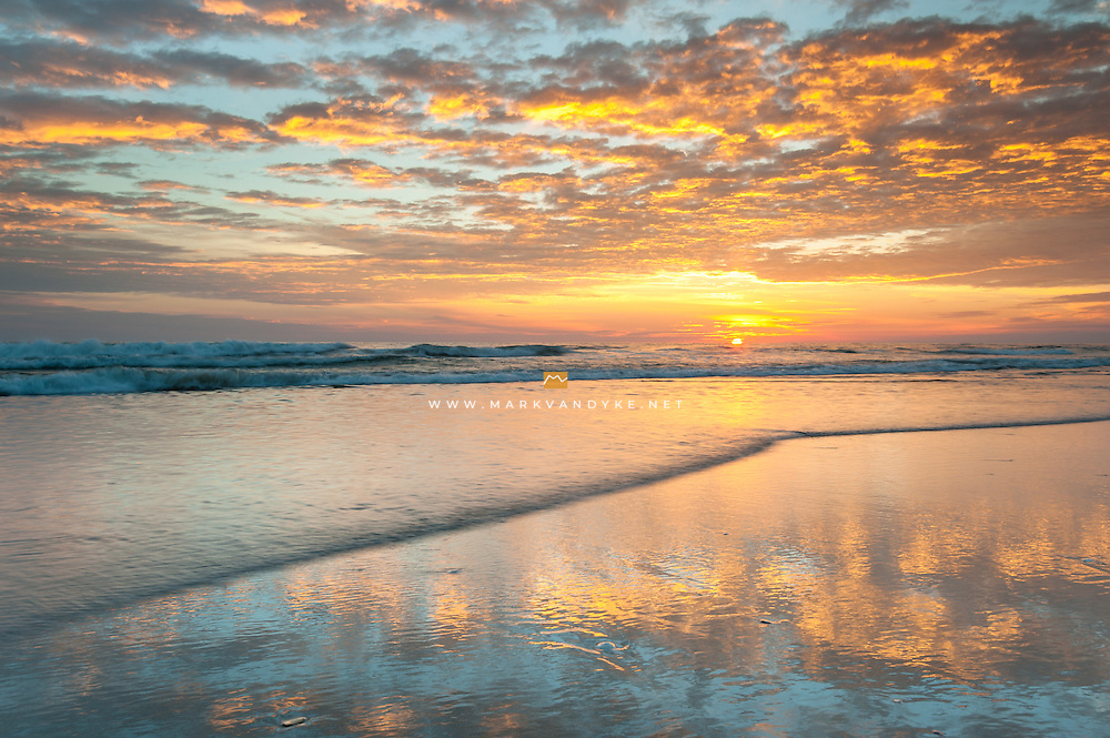 The Atlantic Ocean laps at the beach as the sunrise reflects into wet sands along the Cape Hatteras National Seashore in the Outer Banks of North Carolina.  This chain of barrier islands off the coast of North Carolina is known for its wild and natural beauty.