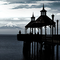 Osorno Volcano Lake Llanquihue in Frutillar, Chile<br /> These people standing on a long wooden pier (Muelle Frutillar) are enjoying a gorgeous scene. In the foreground is Lake Llanquihue. At 330 square miles, this glacier-formed lake is Chile&rsquo;s second biggest. The snowcapped mountain in the background is Volc&aacute;n Osorno. This still active volcano stands over 8,700 feet and is part of the Southern Andes range.