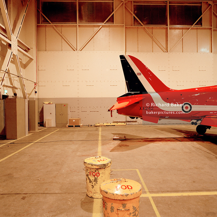 BAE Systems Hawk tail belonging to the elite 'Red Arrows', Britain's prestigious Royal Air Force aerobatic team, forms part of the team's highly-skilled group of support ground crew who outnumber the pilots 8:1. The team's aircraft are in some cases 25 years old and their airframes require constant attention, with frequent overhauls needed. In these shelters were housed the Lancaster bombers 617 Dambusters squadron who attacked the damns of the German Ruhr valley on 16th May 1943 using the Bouncing Bomb. The Red Arrows nearby offices as their administrative nerve-centre for the 90-plus displays they perform a year. .