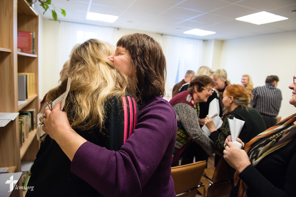 Participants hug during Divine Service on Wednesday, Feb. 4, 2015, at a Diaconia Center mercy project site based at a municipal apartment in Riga, Latvia. LCMS Communications/Erik M. Lunsford