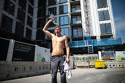 © Licensed to London News Pictures . 26/07/2018. Manchester , UK . Builder CAMERON LAWSON (21 from Bolton) cools off by pouring water over himself during a break on a building site in Trafford . People enjoy the summer sunshine in Manchester as temperatures in the UK are forecast to break records . Photo credit : Joel Goodman/LNP