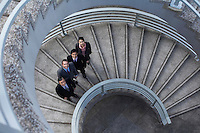 Four business associates standing on spiral staircase portrait