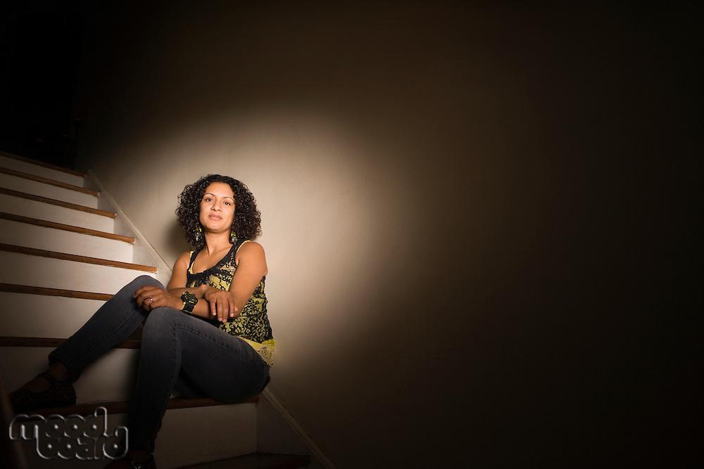 Woman sitting on steps in dark