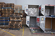 Dented, empty airline freight containers and pallets are stacked up in a Heathrow warehouse car park awaiting the next shipment