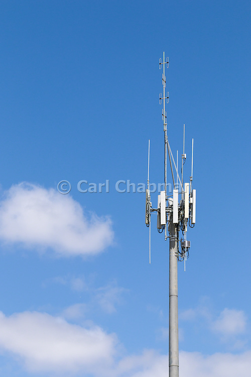 3 sector cellular telecom communications panel antenna array for the mobile telephone system on a cellsite pole tower with two-way radio antennas.
