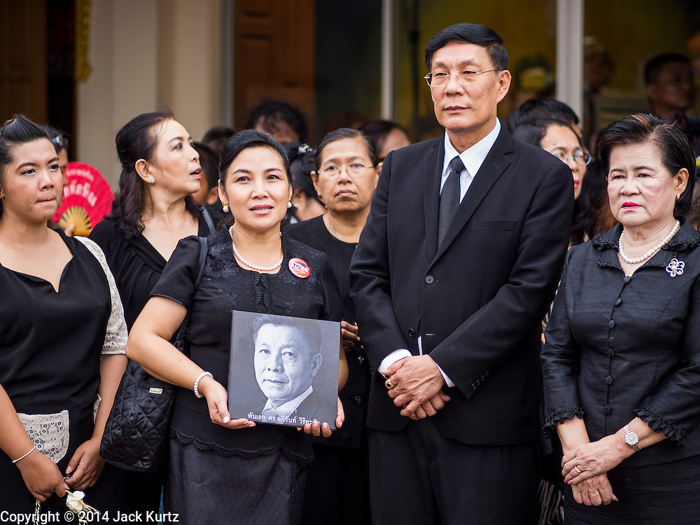 19 OCTOBER 2014 - BANG BUA THONG, NONTHABURI, THAILAND: Mourners carry Apiwan Wiriyachai's portrait during Apiwan's cremation at Wat Bang Phai in Bang Bua Thong, a Bangkok suburb, Sunday. Apiwan was a prominent Red Shirt leader. He was member of the Pheu Thai Party of former Prime Minister Yingluck Shinawatra, and a member of the Thai parliament and served as Yingluck's Deputy Prime Minister. The military government that deposed the elected government in May, 2014, charged Apiwan with Lese Majeste for allegedly insulting the Thai Monarchy. Rather than face the charges, Apiwan fled Thailand to the Philippines. He died of a lung infection in the Philippines on Oct. 6. The military government gave his family permission to bring him back to Thailand for the funeral. His cremation was the largest Red Shirt gathering since the coup.     PHOTO BY JACK KURTZ