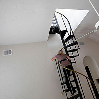 TAMPA, FL -- March 22, 2011 -- Shannon Moore, broker/owner of Green Lion Realty, walks up a spiral staircase in a vacant home in North Port, Fla., 2011.  A recent study showed that one and five homes in the state of Florida is vacant.