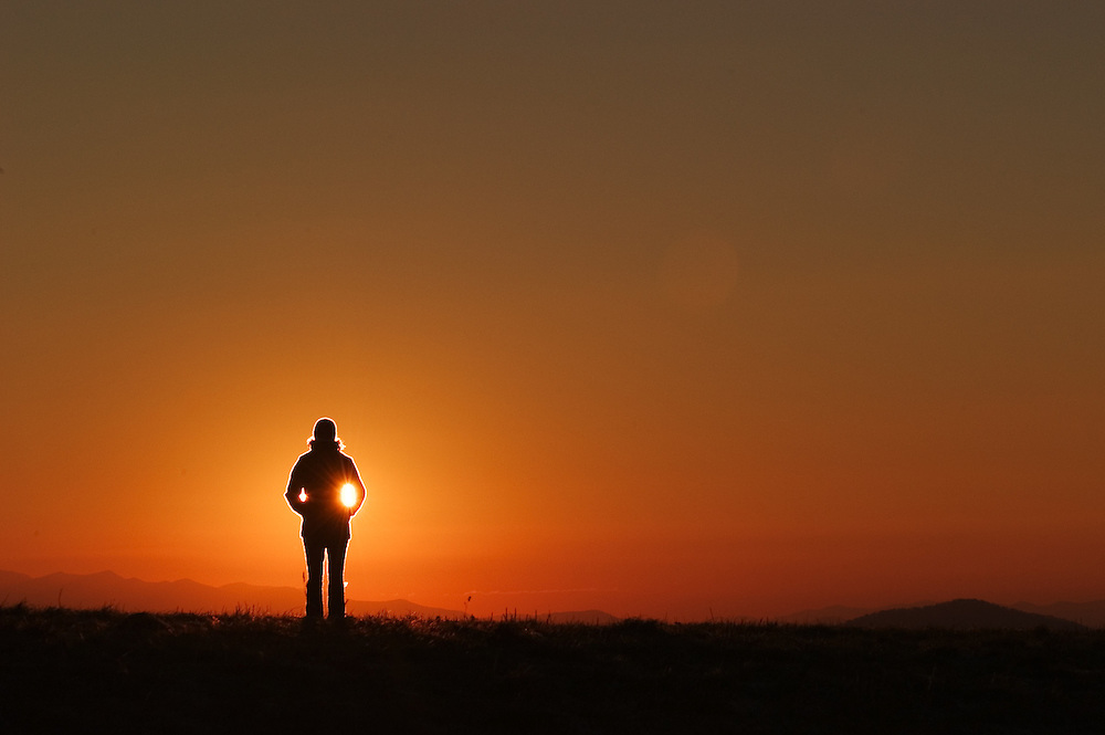 ASHEVILLE, NC - OCTOBER 29: A hiker watches the sunrise over Max Patch on the Appalachian Trail, in the Appalachian Mountains outside Asheville in North Carolina.(Photo by Logan Mock-Bunting) Sunrise on Max Patch, on the Appalachian trail.