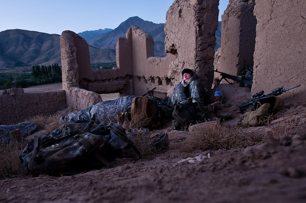 Soldiers wake up after bivouacking in an abandoned Afghan compound during an overnight patrol in the Tangi Valley.