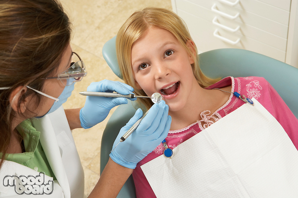 Girl (7-10) having teeth examined at dentists