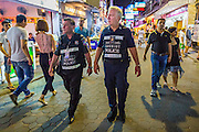 "26 SEPTEMBER 2014 - PATTAYA, CHONBURI, THAILAND: Members of the Foreign Tourist Police Assistants (FTPA) patrol Walking Street in Pataya. The FTPA assist local police in dealing with foreign tourists but don't have arrest powers. Pataya, a beach resort about two hours from Bangkok, has wrestled with a reputation of having a high crime rate and being a haven for sex tourism. After the coup in May, the military government cracked down on other Thai beach resorts, notably Phuket and Hua Hin, putting military officers in charge of law enforcement and cleaning up unlicensed businesses that encroached on beaches. Pattaya city officials have launched their own crackdown and clean up in order to prevent a military crackdown. City officials have vowed to remake Pattaya as a ""family friendly"" destination. City police and tourist police now patrol ""Walking Street,"" Pattaya's notorious red light district, and officials are cracking down on unlicensed businesses on the beach.     PHOTO BY JACK KURTZ"