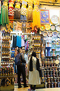 Muslim people at stall selling ceramics and belly dancing costumes in The Grand Bazaar, Kapalicarsi market, Istanbul, Turkey