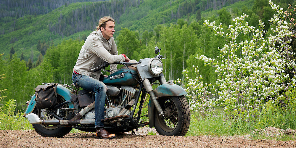 Man in a Gimo's Italian Moto Jacket sitting on Harley Davidson on open country road in the Colorado Rockies