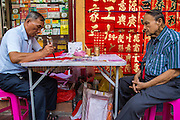 "22 JANUARY 2013 - BANGKOK, THAILAND:  A customer (right) watches calligrapher work on Chinese New Year at his table on Charoen Krung Road in Bangkok's Chinatown district. Chinese New Year is not an official public holiday in Thailand, but it is one the biggest celebrations in the Bangkok, which has a large Chinese population. Chinese New Year is February 10 this year. It will be the ""Year of the Snake.""     PHOTO BY JACK KURTZ"