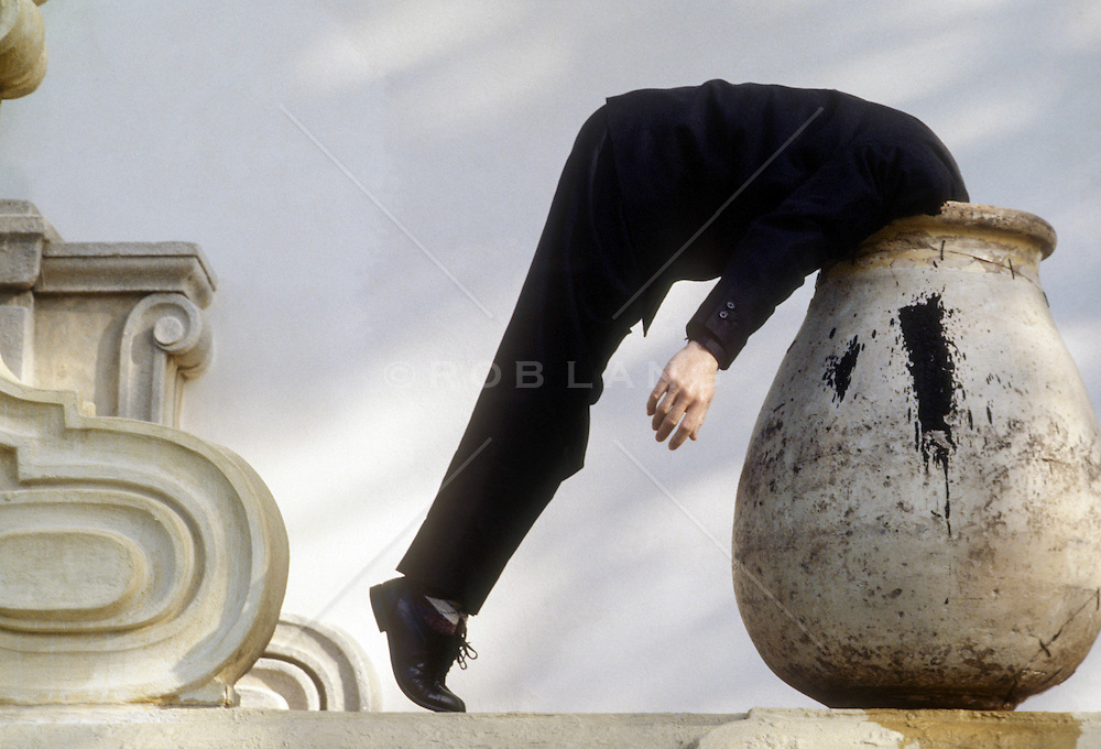 man in black clothes with his head in a large pot
