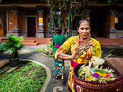 "08 AUGUST 2017 - UBUD, BALI, INDONESIA: A woman prays and in a family compound during a ceremony to honor a family temple in Ubud, Bali. Balinese Hindus have a 210 day calender and every almost every family compound on Bali has a family temple. Once a year (or every 210 days) families celebrate the ""birthday"" of their temple with a ceremony.     PHOTO BY JACK KURTZ"