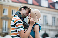 Romantic young man kissing woman against buildings
