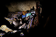 In the village Mataska near Port Loko, Sierra Leone, 8-months pregnant Adamse Bangoa is waiting for the traditional birth attendant to examine her. It is her first pregnancy and this bed in the hut of the birth attendant will be where her delivery will take place. She has never been to the local hospital, a few kilometres away. The birth attendant says: If it is the first birth, we only send them to the hospital after 3 days hard labour.